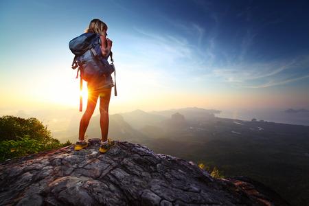 Jonge dame wandelaar staande met rugzak op de top van een berg en genieten van zonsopgang