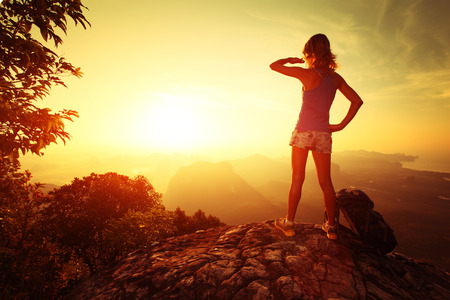 Young lady hiker standing with backpack on top of a mountain and enjoying sunrise photo