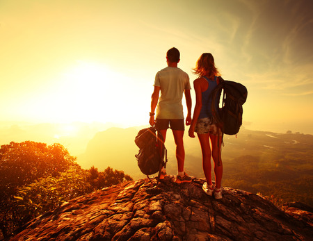 Hikers with backpacks relaxing on top of a mountain and enjoying valley view photo