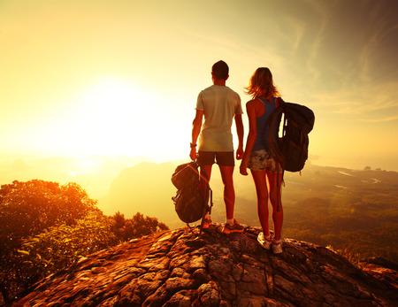 Wandelaars met rugzakken ontspannen op de top van een berg en genieten van uitzicht op de vallei