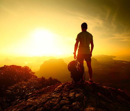 ハイカーのバックパックを山の上に立っていると、日の出を楽しんで