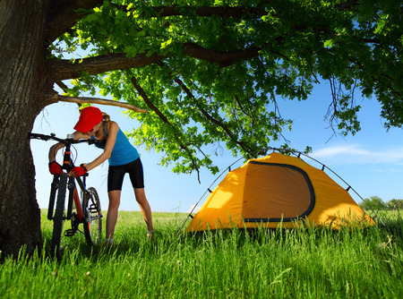 off road biking: Young lady maintaining bicycle on a meadow with green grass