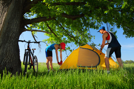 Young couple setting up a tent on a green meadow under big oak photo