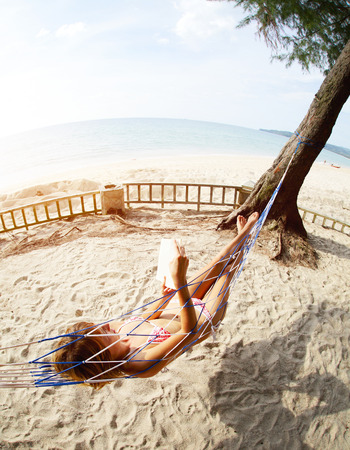 Young lady reading  book in a hammock on tropical beach photo