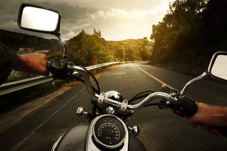 Driver riding motorcycle on an asphalt road through forest photo