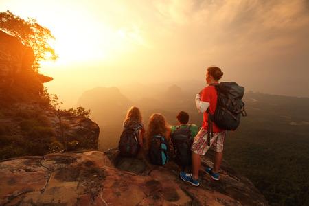 山の上にリラックスして、日の出を楽しんでいるハイカーのグループ 写真素材