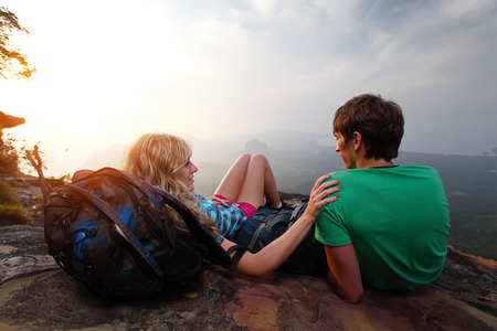 Young hikers relaxing on top of a mountain and enjoying sunrise photo