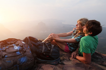 Young couple relaxing on top of a mountain and enjoying sunrise photo