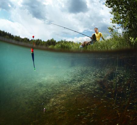 man fishing: Hombre sonriente joven de pesca en la costa de una laguna verde con vista submarina de malezas sobre un fondo de