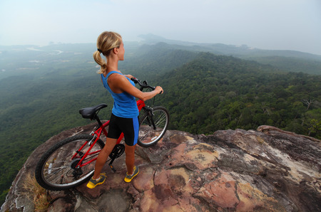 Young sporty lady standing with bicycle on top of a hill and enjoying valley view photo