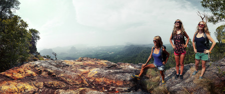woman hiking: Three happy ladies with backpacks standing on top of a mountain and enjoying valley view