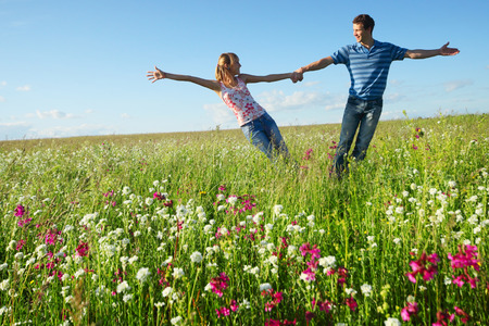 Young couple having fun on a green meadow with flowers photo