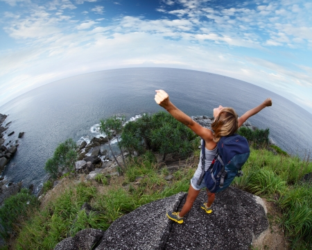 backpackers: Hiker with raised hands standing on top of a mountain