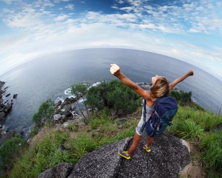 Wandelaar met opgeheven handen staan op de top van een berg