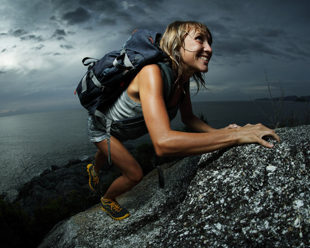 ascend: Hiker with backpack climbing natural rocky wall on a dark cloudy background. There are water drops on the skin