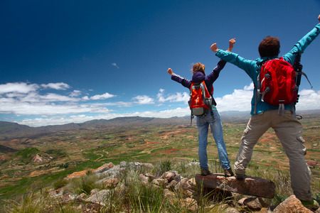 Hikers with backpacks standing on top of a mountain with raised hands Stock Photo - 25583124