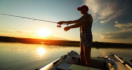 夕暮れ時、ボートからの釣り人