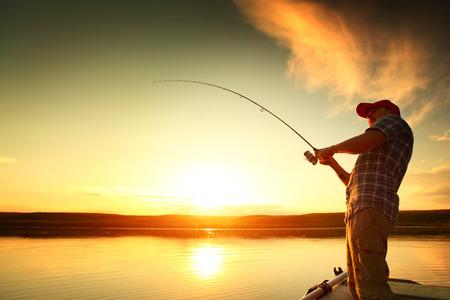 pescador: Hombre joven de pesca en un lago desde el barco al atardecer