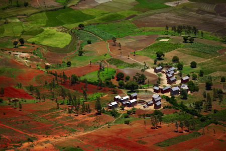among: Traditional Malagasy village among red soils. Madagascar Stock Photo