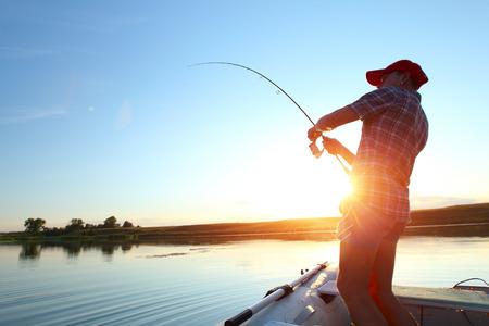 Jonge man vissen op een meer uit de boot bij zonsondergang