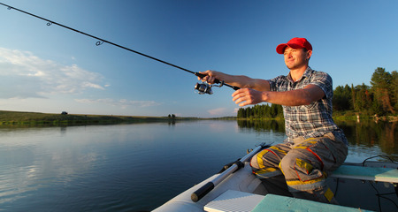casting: Man fishing in a pond from a boat at sunset