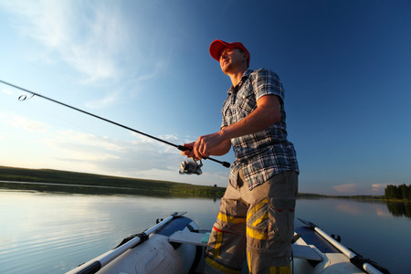 fisherman boat: Man fishing in a pond from a boat at sunset