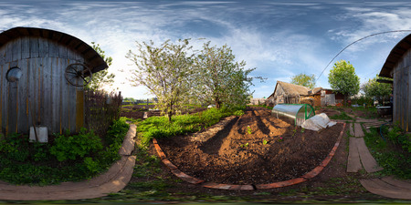 equirectangular: Spherical, 360 degrees panorama (equiregtangular projection) of a spring blooming garden in a village at sunset.
