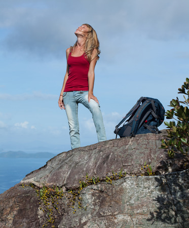 Young lady hiker with backpack standing on top of a mountain photo