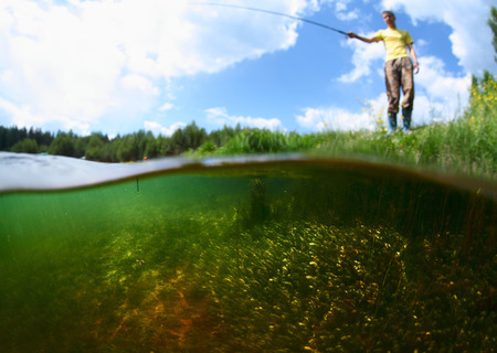 Young man fishing in a pond in a sunny day. Focus on the weed underwater photo