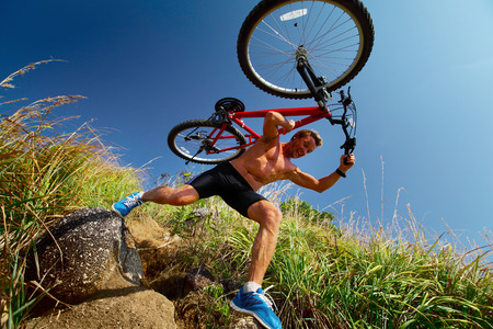 Young athlete crossing offroad terrain with bicycle at sunny day