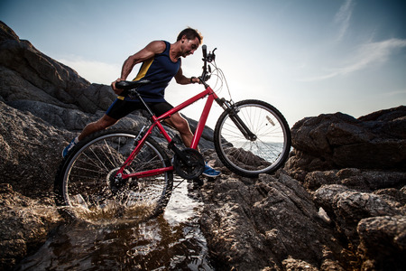 Athlete crossing rocky terrain with water barrier with his bicycle Stock Photo