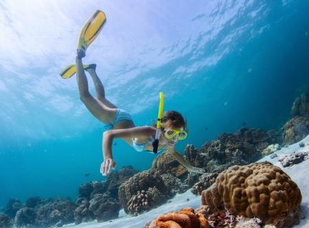 열대 바다의 산호초를 통해 젊은 아가씨 스노클링 스톡 콘텐츠
