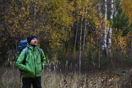 Portrait of the mature backpacker in an autumn forest photo