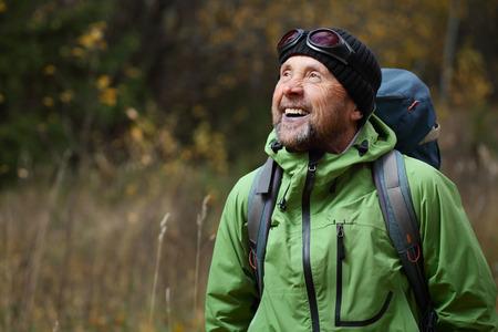 秋の森で幸せの成熟したバックパッカー