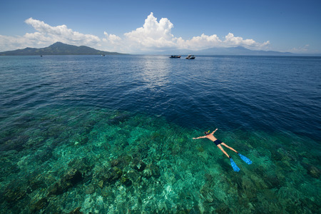 drop off: Man snorkeling in a tropical sea by reefs drop off. Indonesia Stock Photo