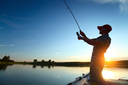 若い男夕暮れボートからの釣り