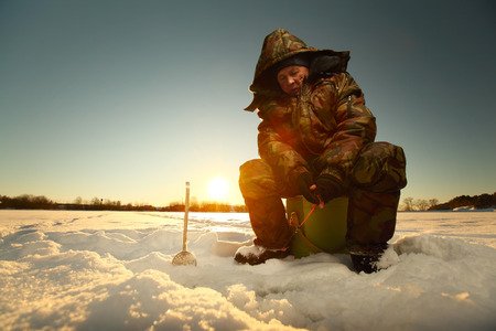 ice fishing: Fisherman on a lake at winter sunny day