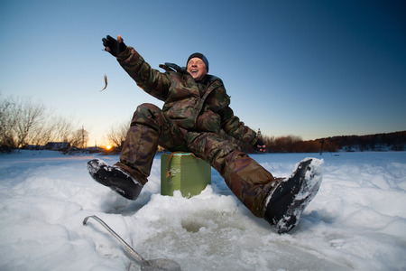 ice fishing: Happy fisherman on a lake at winter sunny day with fish