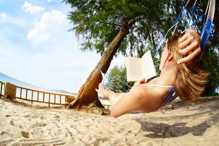 Young woman relaxing with book in a hammock on a tropical beach photo