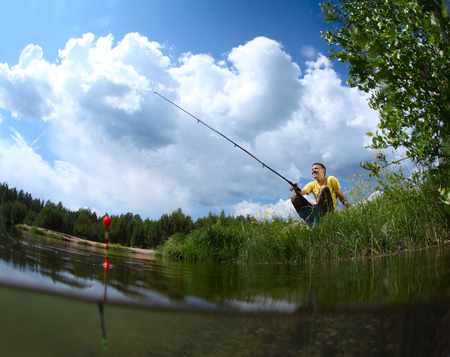 Young man fishing in a pond in a sunny day photo
