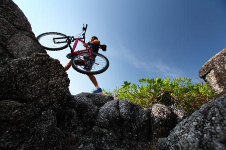 Athlete crossing rocky terrain with bicycle photo