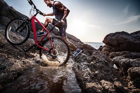 Atleet kruising rotsachtig terrein met waterkering met zijn fiets