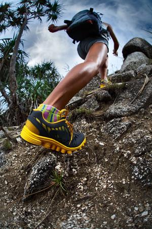 ハイカーのバックパックを自然の岩場を登る