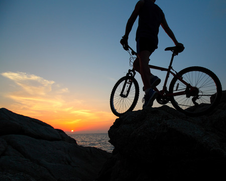 Sportsman with bicycle standing on a rock photo