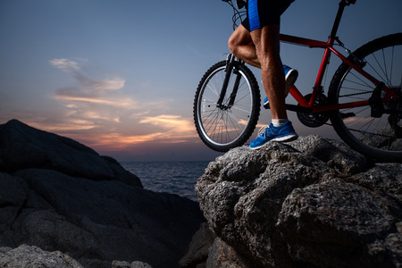Athlete standing with bicycle on a rock at sunset photo