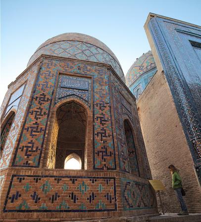 shah: Young lady tourist enjoying oriental atmosphere of ancient complex of Shah i Zinda. Samarkand, Uzbekistan Stock Photo