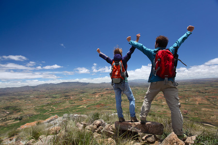 Hikers standing on top of a mountain with raised hands and enjoying valley view Stock Photo