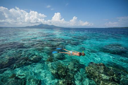 女性は、熱帯の海のサンゴ礁でシュノーケ リングします。インドネシア