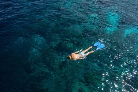 Woman snorkeling in a tropical sea over coral reef. Indonesia Stock Photo - 25584281