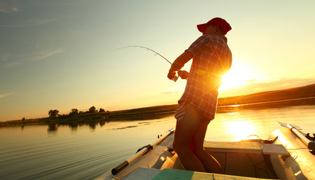 recreational boat: Young man fishing on a lake from the boat at sunset